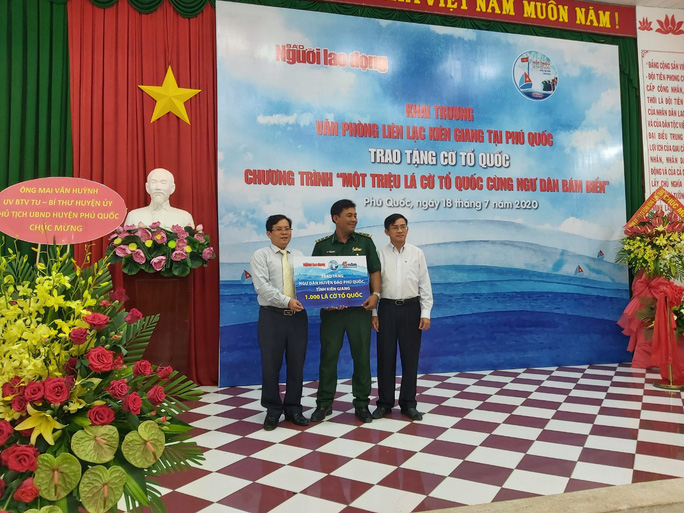 Tổng Biên tập Báo Người Lao Động và đại diện Tổng Công ty Điện lực Miền Nam trao bảng tượng tưng 1.000 lá cờ Tổ quốc cho Ban Chỉ huy Biên phòng cửa khẩu cảng Dương Đông