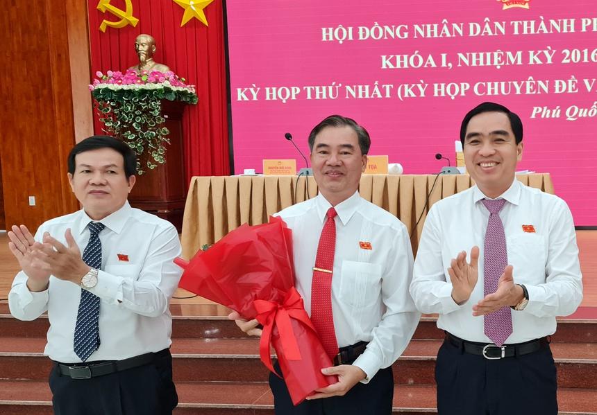 Chủ tịch HĐND TP Phú Quốc Nguyễn Đức Kỉnh (trái) và Chủ tịch UBND TP Phú Quốc Huỳnh Quang Hưng (phải) tặng hoa chúc mừng ông Đoàn Văn Tiến